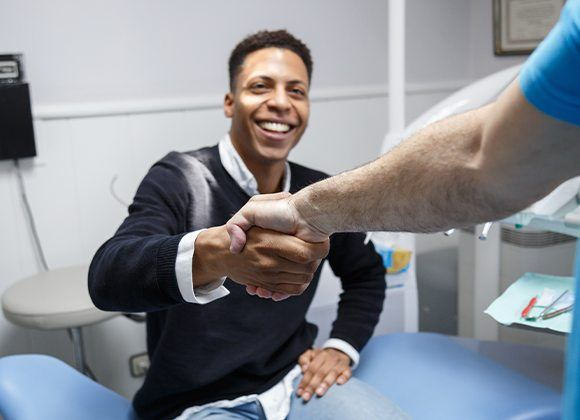 patient shaking dentist's hand
