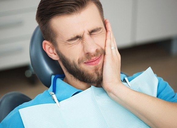 man in blue wincing in pain
