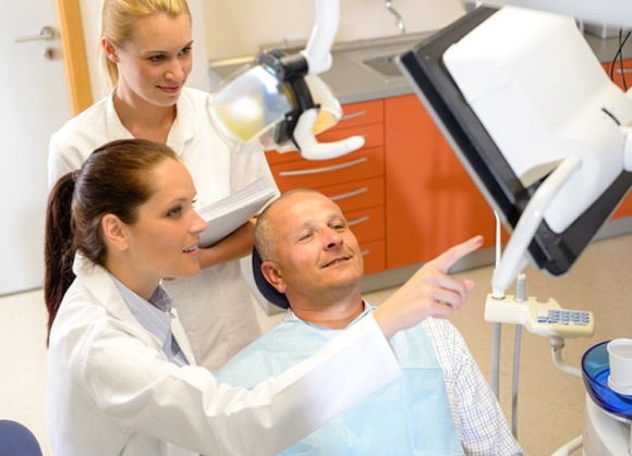 Patient discussing smile makeover with dental office team members