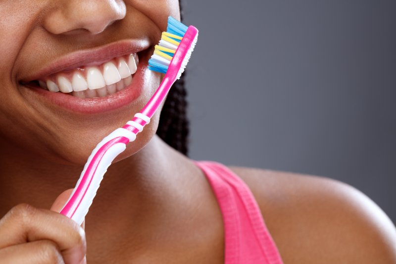 a young woman smiling and holding a manual toothbrush